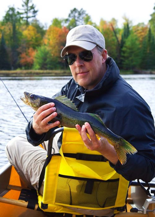 happy-fisherman-holds-up-a-walleye-on-a-northern-m-DN2SM64-resize