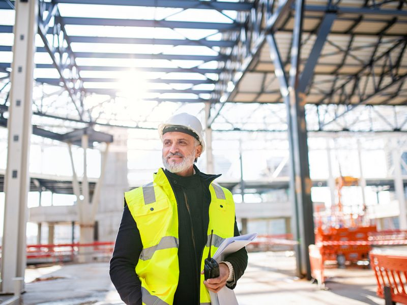 man-engineer-with-walkie-talkie-standing-on-constr-small